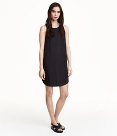 Sleeveless dress in densely woven chiffon with a lined top section and rounded hem.
