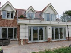 Painswick is fast becoming our most popular colour for the style conscious homeowner. Find out more about Residence Collection colours online. House With Grey Windows, House With Balcony, Green Windows, House Windows, Bedroom Windows, Wooden Cladding Exterior, Brick Cladding, House Cladding, Facade House