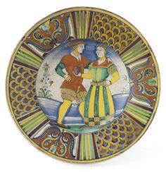 Lot : Grande piatto in maiolica policroma  - Donna che offre un frutto a forma di cuore a[...]   Dans la vente Importants Mobilier et Peintures Anciens & une Prestigieuse Collection de Majoliques à Farsettiarte