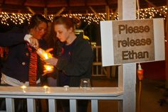 Mileah Lomaneck and Whitley Riley light candles during a candlelight vigil at City Hall in Midland City, Alabama, January 31, 2013. The vigil honored the memory of bus driver Charles Poland, and showed support for the release of a five-year-old boy held hostage in a bunker by Poland's alleged killer. REUTERS/Phil Sears (UNITED STATES - Tags: CRIME LAW)