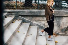 Brown distressed jacket with black straight skirt and sneakers