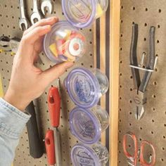 Attach a piece of wood to your wall. Adhere magnetic strips to the wood. Glue washers to the underside of small, clear containers. Put your screws, bolts, nails, etc. inside the containers, cap them, and place them on the wood. The washers will hold tight on the magnetic strip.