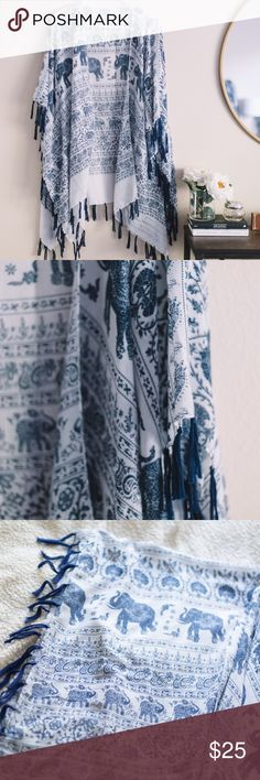 Elephant Tassel-Trim Kimono Style: Lightweight/Delicate Elephant Tassel-Trim Kimono Color: White + Navy Size: One size fits all. Tops