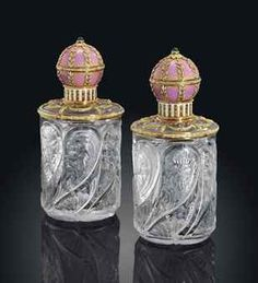 PROPERTY OF A LADY OF TITLE: A PAIR OF GEM-SET ENAMEL THREE-COLOUR GOLD-MOUNTED CUT GLASS SCENT-BOTTLES BY FABERGÉ, MOSCOW, 1899-1908. Each bottle carved with spiral flutes and floral sprays, with two-colour gold ribbon-tied laurel border and green gold ribbon-tied laurel swags suspended from rose gold floral crests, the cover translucent rose over a striped guilloché ground, with cabochon emerald finial on an acanthus mount.