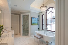 glamorous white master bath dressed in varying textures of calacatta and carrera marble