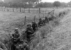 German soldiers move through an irrigation ditch on their way to the front. Arnhem, Netherlands. September 1944.
