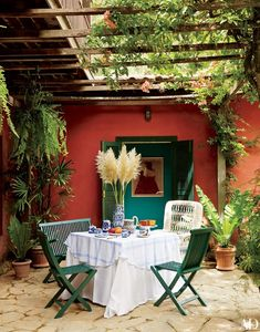 A vine-covered trellis tops a dining terrace at the Brazil retreat of Valentino brand ambassador Carlos Souza; the artwork visible through the doors is a Fernando Botero drawing of a woman in a Valentino dress.