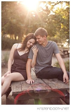 smiles, head on shoulder, center beaming light at top of photo, out of focus in back, wooden table and landscape
