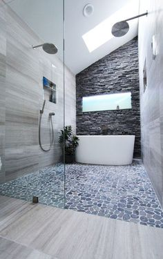 Stunning walk-in shower featuring a stacked-stone wall, pebbled tile, large shower heads and a white freestanding tub | Change Your Bathroom, Inc.