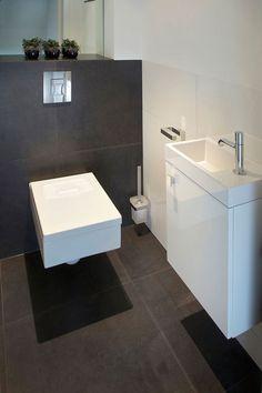 Een mooi toilet ontwerp met een zwarte mozaïek wand en granieten fonteintje