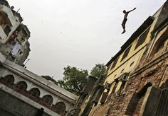 A man dives into a pond from atop a building to cool himself on a hot afternoon in New Delhi, May 8, 2012. (Kevin Frayer/Associated Press)  #
