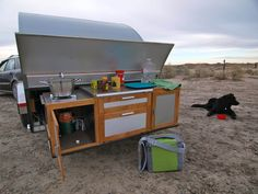 """Mary purchased her 5×10 foot teardrop for $4,000 from an """"octogenarian craftsman"""" in Nebraska who builds one teardrop trailer a year. The 550 lb. trailer has a full-sized bed with a memory foam mattress and storage space underneath, a fold-up table, two feet of floor space, drawers, cabinets and counter space. Outside, in the back, is a slide out kitchen/galley area with plenty of storage space for pots, pans and food and a propane burner for cooking. The trailer is insulated and has a large…"""