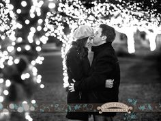 Kevin giving Kate a forehead kiss amongst lighted trees. Milwaukee Engagement Photography - Winter Photo by: FRP