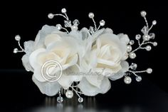 A simple but sparkly wedding flower comb of two organza and poly fabric flowers complimented by pearl, crystal bead and rhinestone sprays. it is about 5 inches long and 3 inches high.