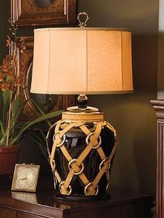 """Complete with painted """"leather"""" straps, the Brookline Ceramic Lamp provides any room in your home with a warm glowing light and elegant style."""