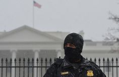 A member of the Secret Service Uniform Division stands guard in front of the White House under snowfall on Tuesday, Jan. 21, 2014, in Washington, D.C. The U.S. government shut down Tuesday as a major snowstorm threatened to dump as much as 10 inches on Washington by day's end.