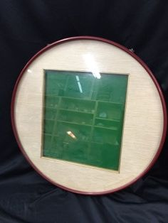 VINTAGE CIRCLE-SHAPED PICTURE FRAME WITH FABRIC MATTING. THERE APPEARS TO BE A WATER STAIN ON THE BOTTOM RIGHT AREA OF THE MAT. MEASURES 18 IN. DIAMETER.
