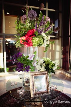 Beautiful arrangements to display the beautiful brides portraits. These arrangements include purple clematis, coral charm peonies, larkspur, hydrangea bud, and bells of Ireland. Floral and Decor: College Flowers, Lubbock, TX Photography: Lauren Clark Photography