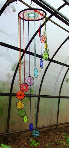 Unique chandelier inspired dream catcher. Instead of classic feathers and other trinkets hanging, this one is designed with the colorful circle hanings dropping down.