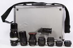 Lot 567: Vivitar and Nikon Camera Lens Assortment; Including five Vivitar lenses and three Nikon lenses; together with a hard metal case and six lens cases