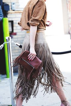 Street chic style: Statement-making fringe bag and fringe skirt. Click to see more leather fringe skirts.