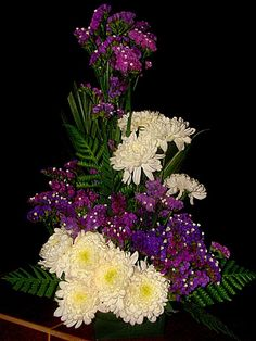 White mums and purple statice flowers.
