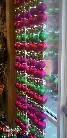 Christmas window treatment - get cheap ornaments at the dollar store, hang on fishing wire, knotting around the loop on each one, and then attach to a tension rod to display in window