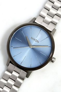 "Define your style with a luxe accessory like the Nixon Kensington Silver, Sky, and Gunmetal Watch! This classic design features a blue watch face with dainty silver time markers and hands, surrounded by a 1.5"" beveled gunmetal setting. Watch has an 8"" circumference (closed), plus 1"" of extra links included. Water resistant up to 50 meters."