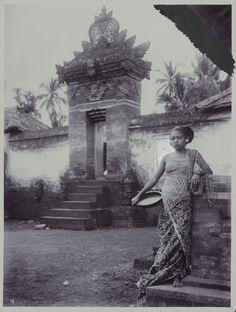 Een Noord-Balinees meisje staand voor een poort