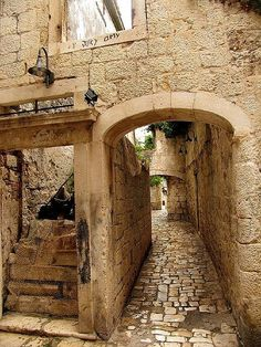 "A passageway in the Croatian coastal island town of Trogir (Croatian, ""Trogir""), whose 2,300-years-old heritage reflects the influences of Greeks, Romans, and Venetians. In 1997, its center ..."