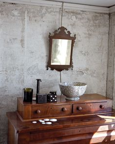 In an upstairs bedroom, a Federal mirror hangs above an Empire bureau displaying a transferware bowl, a collection of sand dollars, folk-art dice, and a Cire Trudon candle from Derian's store. The walls are made of horsehair-and-seashell plaster and are original to the house. Derian left them bare after stripping the room of wallpaper.