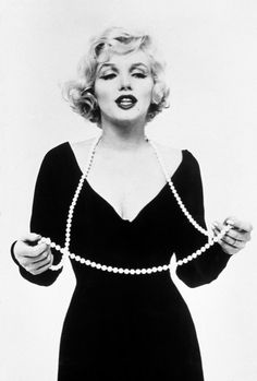 Marilyn Monroe JANUARY 1961 – Red lips parted and wearing a plunging black dress, Monroe delicately holds a set of pearls