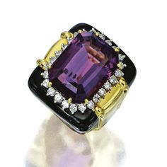 AMETHYST, DIAMOND AND ENAMEL RING, DAVID WEBB Centering an emerald-cut amethyst weighing approximately 20.00 carats, framed by 26 round diamonds weighing approximately 1.00 carat, accented with black enamel and polished gold, mounted in 18 karat gold and platinum, signed Webb.