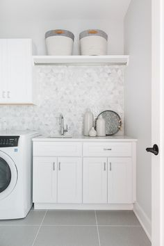 Gray grid floor tiles complement white shaker cabinets adorned with polished nickel pulls and a white quartz countertop in a well appointed white and gray laundry room clad in white and gray diamond pattern wall tiles. Gray grid floor til Laundry Room Tile, White Laundry Rooms, Modern Laundry Rooms, Laundry Room Cabinets, Laundry Room Storage, Room Tiles, Basement Laundry, Garage Laundry, Armoires Shaker