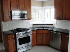 White subway tile backsplash. Black countertop. Medium dark cabinets. Replace with white appliances.