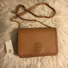 """Tory Burch Marion Combo Crossbody Tory Burch Marion Combo Crossbody in bark!  can be worn over the shoulder or across the body or carried as a clutch when you remove the chain-adorned strap. Made of pebbled leather, the compact shape is perfectly sized to hold small essentials, with interior pockets. Flap with magnetic snap closure. Adjustable, removable cross-body strap with 23""""  drop. 1 exterior zipper pocket under flap. 1 interior zipper pocket, 2 open pockets. H: 5"""" L: 8"""" D: 2""""  100%…"""