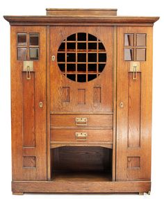 EUROPEAN CONTINENTAL ARTS & CRAFTS OAK WARDROBE, CIRCA 1900, the projecting cornice above a single door with glazed panel above two drawers and an open shelf and two further doors, the whole raised on a plinth base, 155cm wide, 192cm high, 46cm deep
