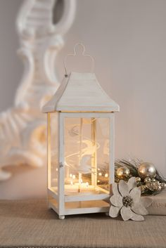 """Changing Seasons Lantern  P91111   $85.00 Traditional lantern shape with a clever update – heat from tealights spin the removable metal insert. Display the soaring birds insert for the spring and summer and swirling snowflakes for the colder seasons. Or, remove the insert and use lantern with a pillar candle. All candles sold separately. Metal with an antiqued finish. 14¼""""h, 6¾""""w."""