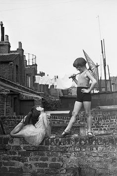Two young ballet dancers, Violet Hutchinson aged 8 and Betty Putt aged 7, rehearsing in a back garden in Poplar, east London. Despite a lack of space, children played in the streets and backyards often improvising with anything lying around – the only limit being their imaginations.
