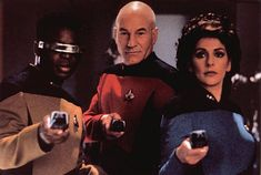 La Forge, Picard, and Troi with Phasers at the ready.