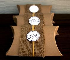 "4.5"" x 4.5"" x 1.5"" DIY Pillow Boxes. Kits come pre-adorned with jute/raffia. White circles can be personalized with initials and/or date! Any quantity available. Made to order. Hand crafted. #wedding #favors #idea See more here: https://www.etsy.com/listing/105742720/burlap-pillow-boxes-100-rustic-wedding?ref=shop_home_active_5"