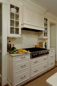 Like hood over range with glass front cabinets flanking hood. Like how hood protrudes to provide dimension and 'hide' vent.