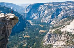 """A hiker on """"The Visor"""" on the summit of Half Dome, Yosemite National Park."""