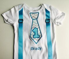 This Baby boy 1st Birthday Tie Outfit has a red and white chevron tie. There is a 1 appliqued on the tie in aqua and your babys name can be put below the tie. Aqua suspenders finish the outfit.. The suspenders have real suspender buckles.  (Please note if I run out of the current tie will substitute a similar material.)  This Super cute baby boy shirt can be personalized to include your Little Ones name. This is a super cute baby boy outfit. This baby clothing comes in a variety of sizes…