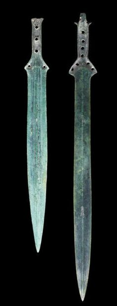 Two European bronze swords  Late Bronze Age, circa 900 B.C. The larger leaf-shaped blade with pronounced central ridge with two grooves to either side at the tip, with two notches above the wings of the hilt-plate, the hilt pierced with four rivet-holes, terminating in a faint 'fish tail' tang, 23in (58.5cm) long; the shorter with a stepped central ridge, with a single notch above the hilt plate, the hilt pierced with three rivet holes, 18¾in (48cm) long (2)