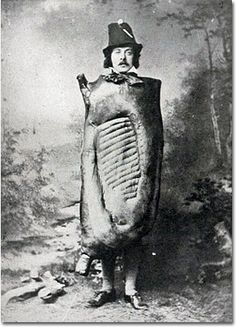 This stone-faced man in a wacky meat costume is George J. Nicholls, author of the 1917 book Bacon and Hams, posing for the dust jacket photo of that very book. He clearly wanted to leave no question of his authority on the subject.    In the text of the bio, he was equally sure to note that his side-of-bacon costume won first prize at the 1894 Covent Garden Fancy Dress Ball