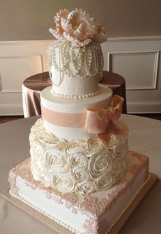 Vintage-themed pink and white wedding cake with bows, roses, and pearls #weddingcake #cake #vintagewedding #pink #elegant