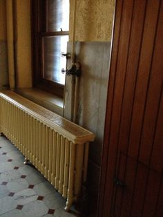 White cast-iron radiator and pressure taps just inside the door of the Laundry Room in the James J. Hill House's servants' quarters.