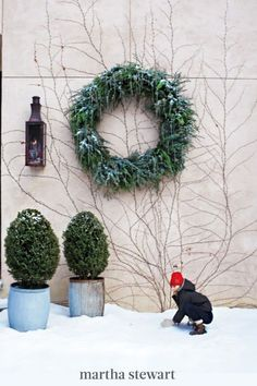 Decorate a cedar-and-juniper wreath with icicle ornaments and let it greet your guests all winter long. Wrap floral wire through the ornament's hole and around the greenery, and be sure to place more of the shiny spikes along the upper arc for a winter wonderland. #marthastewart #christmas #diychristmas #diy #diycrafts #crafts