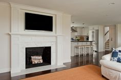 Light and bright Family room fireplace with Tv above, functional and beautiful D Thomas Scott - white marble  fireplace surround,